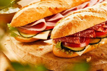 Deux baguettes fraîches et savoureuses garnies de viande, l'une avec du salami et l'autre avec du jambon, avec du fromage et des garnitures de salade servies sur une planche de bois Banque d'images - 75988930