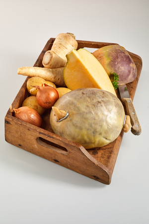 Preparing haggis with neeps and tatties in an overhead view of an uncooked haggis with fresh turnips, swedes, onion and potato ingredients on a wooden tray