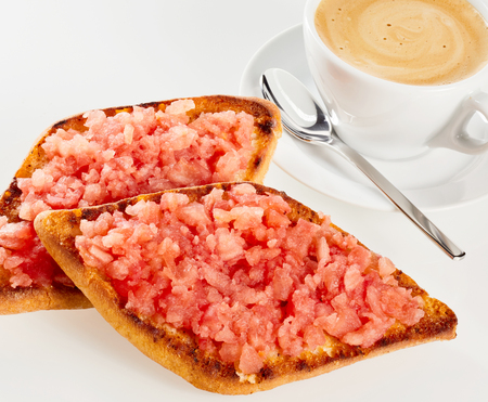 Fresh salsa on a deep fried crunchy tostada served with frothy milky coffee over a white background Stock Photo