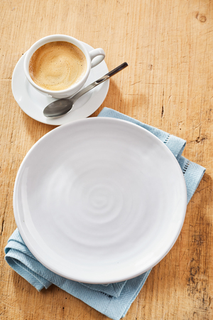 Top view of white round plate on blue napkin and cup of coffee with tea spoon on wooden surface. Stock Photo