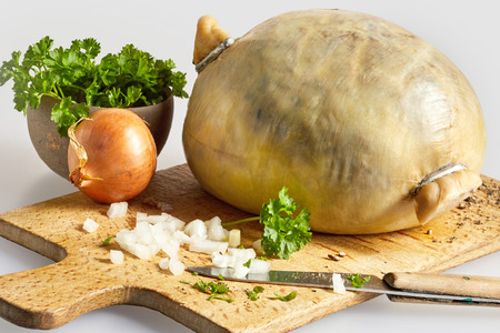 Raw haggis ready for cooking with diced fresh onion and coriander on a wooden cutting board in a close up view of Scottish cuisine
