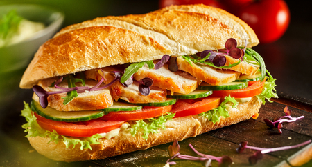 Side view of delicious fresh chicken baguette with salad next to ingredients