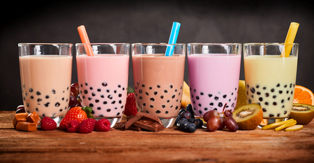 Row of fresh boba bubble tea glasses on wooden background. Slices of fruity ingredients with delicious glasses of a summer refreshment.