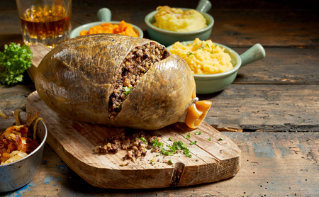 Cooked sliced open haggis and vegetables with mashed turnip, potato and fried onions on a rustic wood table with copy space Stockfoto