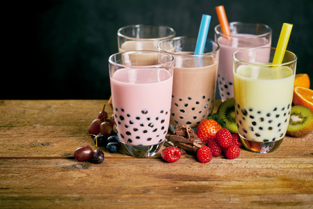 Assortment of milky bubble teas with fresh fruit ingredients served with wide straws on a wooden table with copy space Archivio Fotografico