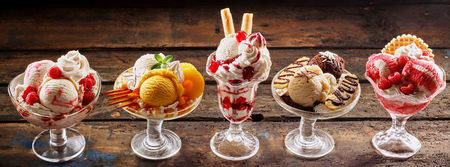 Row of gourmet ice-cream desserts in banner format with Italian gelato with fresh fruit garnishes including cherry, raspberry, strawberry, mango, pineapple, vanilla, chocolate, caramel and banana