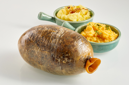 Cooked Scottish haggis with neeps and tatties, or mashed turnip and potato, served in side dishes over a white background Stock Photo