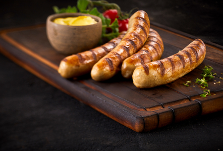 Four succulent grilled pork sausages served with a mustard dressing and fresh herbs on an old vintage wooden chopping board with copy space Stock Photo
