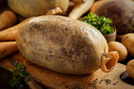 Raw Scottish haggis made of minced offal mixed with seasoning, suet, oatmeal and onion stuffed into a sheep stomach on a wooden chopping board with ingredients behind