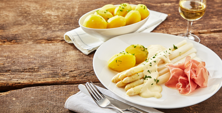 Plate of cured ham with white asparagus tips dressed with creamy mayonnaise and parsley or coriander served with boiled potatoes and white wine
