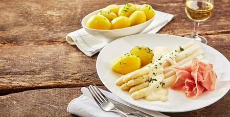 Plaat van gerookte ham met witte aspergepunten, bekleed met romige mayonaise en peterselie of koriander, geserveerd met gekookte aardappelen en witte wijn Stockfoto - 75988933