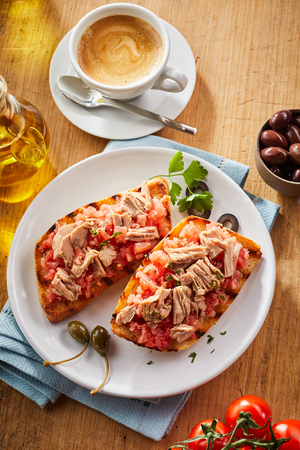 Tuna and salsa topping on fried tostrada, or tortilla, garnished with olives and fresh herbs and served on a plate surrounded by ingredients and a cup of coffee