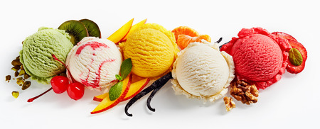 Row of colorful ice cream scoops with decorations, shot from above, isolated on white background