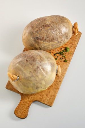Two uncooked Scottish haggis on a wooden board with freshly chopped herbs viewed high angle over white with copy space Imagens