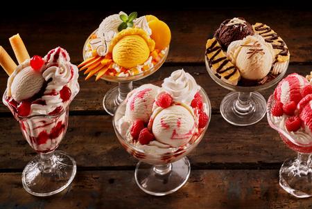 Assortment of fruity ice-cream sundae desserts made of artisanal Italian gelato garnished with cream and fresh, strawberries, raspberries, mango, pineapple, banana and cherries