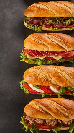 Satz von vier kompletten Feinkostgeschäftart-Sandwichen füllte mit verschiedenen Arten von Fleischscheiben und -gemüse über dunklem Hintergrund