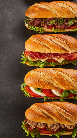 Set of four complete deli style sandwiches filled with various types of meat slices and vegetables over dark background