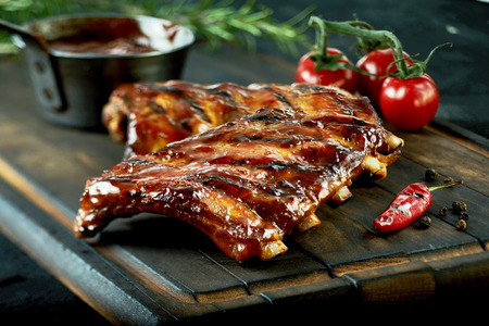 Spicy hot grilled spare ribs from a summer BBQ served with a hot chili pepper and fresh tomatoes on an old vintage wooden cutting board Archivio Fotografico