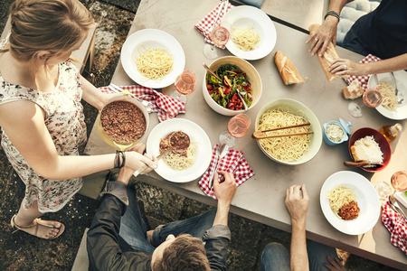 spread around: Group of young friends enjoying an outdoor meal together around a table spread with spaghetti pasta, beef bolognaise sauce and fresh bowls of salad viewed from above Stock Photo