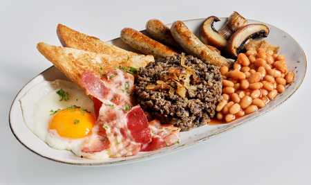 Traditional Scottish meal with haggis and beans served with toast , fried egg, bacon, mushrooms and sausages for a wholesome breakfast Stock Photo