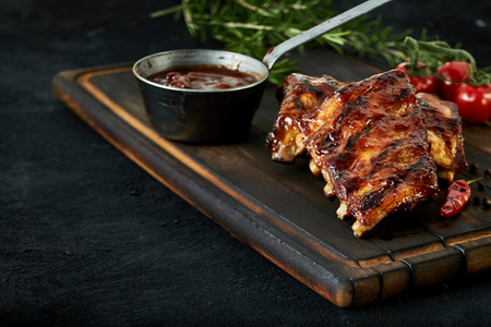 Spicy rack of spare ribs with marinade in a small saucepan and a red hot chili pepper served on an old wood chopping board in a restaurant , close up view with copy space Archivio Fotografico