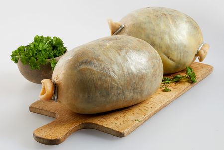 Two uncooked haggis on a chopping board with fresh parsley or coriander in a concept of regional Scottish cuisine Imagens