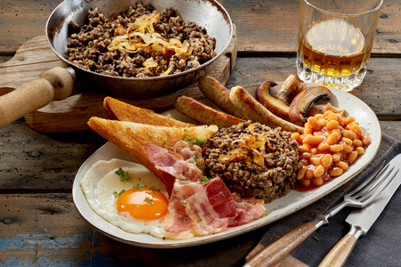 Meal of Scottish haggis, toast, beans, fried egg, bacon, mushrooms and pork sausages served with whisky on a rustic wooden table