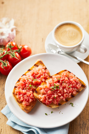 Tasty tostada snack topped with salsa and fresh herbs served on a white plate with coffee viewed from above