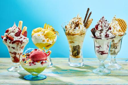 5 つの異なる味の青い背景のライトの木製テーブルのアイス クリーム サンデー