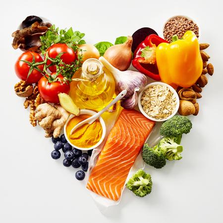 하트 모양의 정물화 된 건강한 음식의 심장과 심장 혈관 시스템에 신선한 성분이 풍부한 항산화 물질과 위에서 본 오메가 -3 지방산에 고립 된 흰색