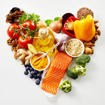 Heart-shaped still life of healthy food for the heart and cardiovascular system with fresh ingredients rich in antioxidants and omega-3 fatty acids viewed from above isolated on white