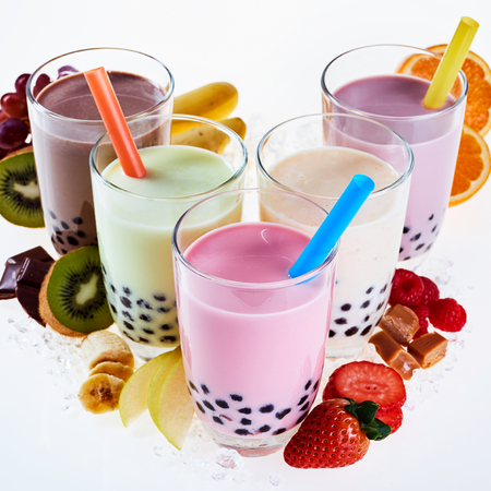 Assorted flavors of milky bubble or boba tea made with tapioca pearls and fresh fruit ingredients, chocolate and caramel served in glasses with straws and crushed ice Stock Photo