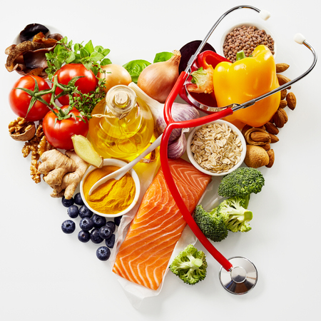 Fresh food for a healthy heart concept with a heart-shaped arrangement of salmon, herbs, nuts, spices, oats, tomato, blueberries, bell peppers and olive oil with a colorful red stethoscope on white