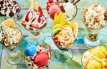Assortment of different flavor Italian ice cream sundaes on wooden table