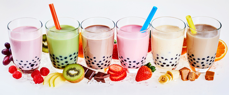 pearl tea: Selection of fruit flavored bubble or boba tea with fresh ingredients alongside arranged in a line isolated on white in a panoramic banner format for advertising or a header Stock Photo