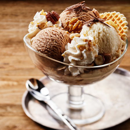 Tasty ice cream dessert made from chocolate and strawberry flavors with nuts and waffle cracker in glass bowl Imagens
