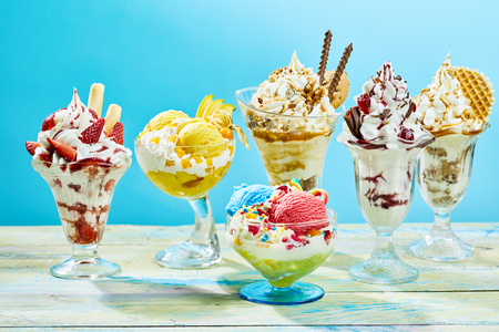 Five different flavor ice cream sundaes on light wooden table with blue background