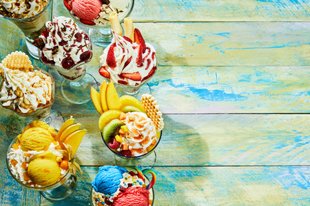Elevated view of different flavor ice cream sundaes on wooden table with copy space