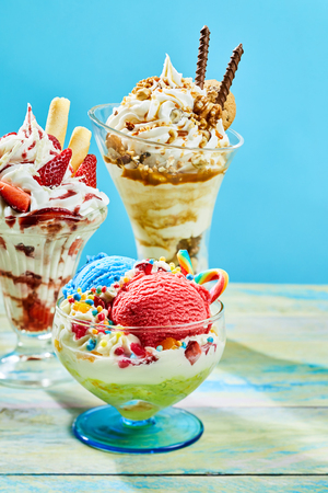 Three different flavored delicious ice cream sundaes on table with blue background Stock Photo