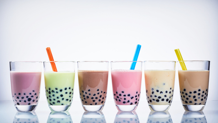 Colorful selection of milky fruit flavored bubble tea arranged in a line on a reflective white surface in panoramic banner format with copy space