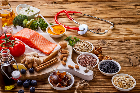 Eating for a healthy heart concept with a stethoscope alongside an arrangement of raw salmon,oats, lentils,ginger, nuts, blueberries , broccoli, tomato, soy sauce, olive oil and herbs on rustic wood Stock Photo