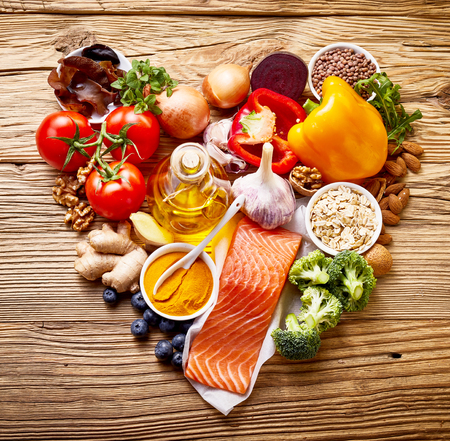 Healthy diet concept for the heart and cardiovascular system with assorted fresh foods rich in omega-3 fatty acids and antioxidants arranged in a heart-shaped still life on rustic wood top down view