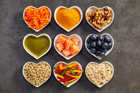 Gezond eten voor het hart met rijen hartvormige gerechten met haver, kurkuma, walnoten, zalm, acai, wortel, linzen, paprika en olijfolie van bovenaf gezien Stockfoto