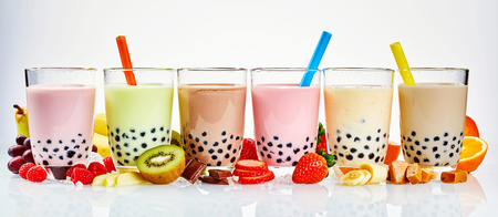 Asian tea house advertising banner of a choice of different flavored boba teas surrounded with fresh fruit ingredients, and caramel and chocolate candy in a wide panoramic header format on white Stockfoto