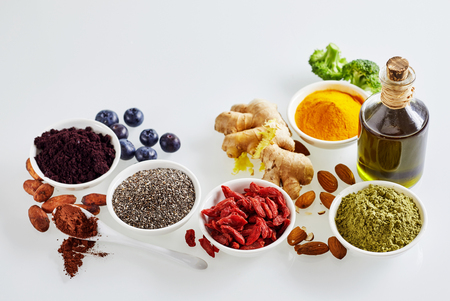 Still life arrangement of superfoods for a healthy diet and heart with acai berries , cacao, goji, chia , turmeric, curcuma, root ginger, virgin olive oil, broccoli and almonds in a high angle view Stock Photo
