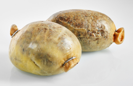 Pair of ready to eat haggis sealed in the stomach of a sheep over neutral background