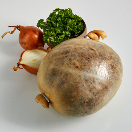 Cup full of raw parsley and two onions beside haggis. The casing is from the stomach of sheep and filed with organ meat. Imagens