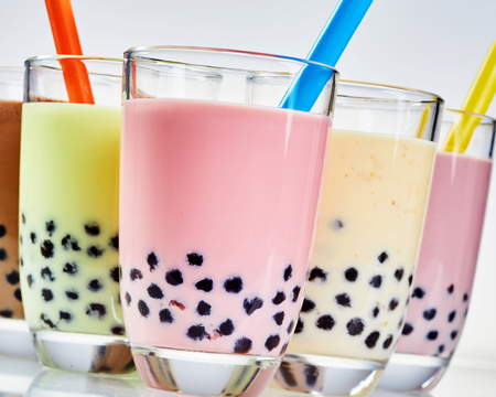 Close up detail of tapioca pearls in bubble tea flavored with fresh fruit and milk and served in glasses with a straw