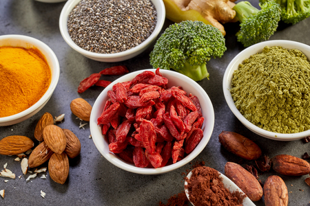 adequate: Selection of healthy nutritious superfoods for a healthy diet and heart with dried goji berries, chia seeds, turmeric, curcuma, ginger, broccoli and almonds in a close up view