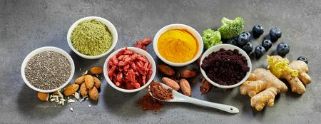 Superfoods acai, 브로콜리, 카 카오, goji 열매, chia 씨앗, 심 황, curcuma, 생강, 계 피와 질감 된 회색 배경에 아몬드의 정물화와 건강 한 식단에 대 한 파노라